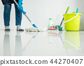 Young housekeeper cleaning floor mobbing holding mop and plastic 44270407