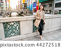successful woman watching others on footbridge 44272518