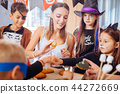 Children wearing Halloween costumes making sweets for party with teacher 44272669