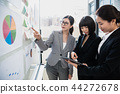 Concentrated businesswomen using pad at office 44272678