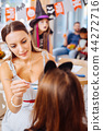 Dark-haired teacher wearing white striped dress painting faces of children 44272716