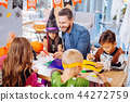 Smiling father helping his children painting bats and spiders for Halloween 44272759