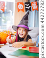 Girl wearing wizard Halloween costume laughing while drawing scary pictures 44272782