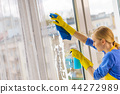 Woman cleaning window at home 44272989
