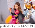 Funny fashionable girl wearing Halloween dress standing near her wall calendar 44273393