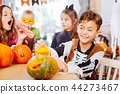 Dark-haired boy wearing skeleton costume for Halloween opening little pumpkin 44273467