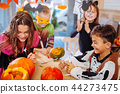 Four children attending Halloween celebration coloring pumpkins together 44273475