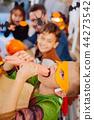 Cute boy wearing Ninja turtle costume for Halloween playing tricks eating sweets 44273542