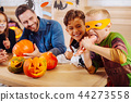 Blonde-haired boy wearing Ninja turtle costume playing tricks eating hand cookie 44273558