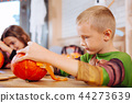 Boy wearing Ninja turtle costume feeling entertained while decorating pumpkin 44273639
