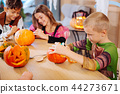 Blonde-haired boy wearing Ninja turtle costume for Halloween decorating pumpkin 44273671