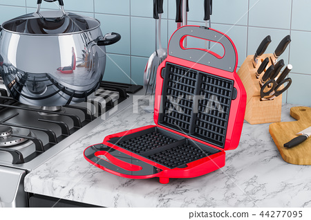 Opened waffle iron closeup on the kitchen table 44277095