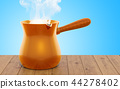 Turkish coffee pot with coffee on the wooden table 44278402