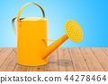 Yellow watering can on the wooden table 44278464