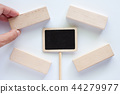 Hand picking the wooden toy with label stick 44279977