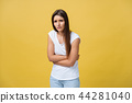 Indoor portrait of cute girl standing with crossed hands on belly, feeling awkward or suffering from 44281040