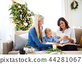 A small boy with mother and grandmother looking at photos at home at Christmas time. 44281067