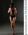 Slim woman in bdsm style dancing on pylon 44282068