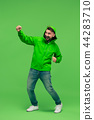 handsome bearded young man looking at camera isolated on green 44283710