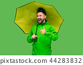 handsome bearded young man holding umbrella and looking at camera isolated on white 44283832
