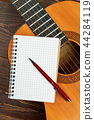 Guitar with blank notebook and pen. 44284119