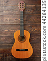 Acoustc guitar on brown wooden background. 44284135