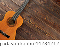 Acoustic guitar on textured wooden background. 44284212