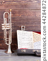 Trumpet and musical notes on wooden background. 44284872