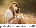 Beautiful carefree woman in fields being happy outdoors 44285500