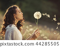Beautiful young woman blows dandelion in a wheat field in the summer sunset. Beauty and summer 44285505