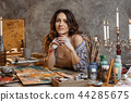 The attractive girl brunette with long hair, is in its creative workshop where she draws and makes 44285675