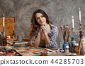 The attractive girl brunette with long hair, is in its creative workshop where she draws and makes 44285703