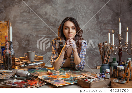 The attractive girl brunette with long hair, is in its creative workshop where she draws and makes 44285709