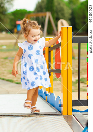 Pretty little girl plays outdoor on a summer day. 44286928