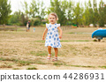 Pretty little girl plays outdoor on a summer day. 44286931