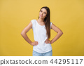 Studio shot of attractive self confident young female in great mood feeling happy, holding hands on 44295117