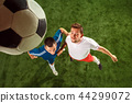 Football players tackling for the ball over green grass background 44299072