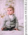 Cheerful little baby boy playing near Christmas tree 44301821
