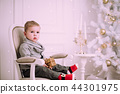 Cheerful little baby boy playing near Christmas tree 44301975