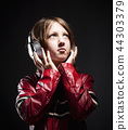 Boy with Blond Hair Listening to Music 44303379