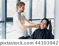 A woman in a hairdressing salon waiting to see the results looking in a mirror, smiling and talking 44303942