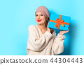 girl in white sweater with gift box 44304443