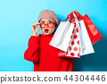 girl in red sweater with shopping bags 44304446
