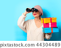 girl in white sweater with binocular and gift boxes 44304489