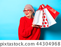 girl in red sweater with shopping bags 44304968