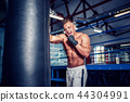 Male boxer training with punching bag in dark sports hall. 44304991