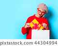 girl in red sweater with gift box and shopping bag 44304994