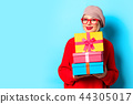 young girl in red sweater with gift boxes 44305017