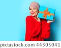 young girl in red sweater with gift box 44305041