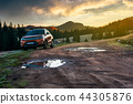 suv parked on the road near forest at sunrise 44305876